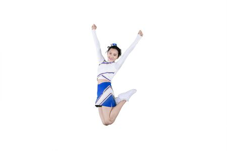 Portrait of pretty cheerleader girl smiling at the camera while jumping in the studio, isolated on white background Stock Photo