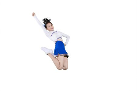 Portrait of Asian cheerleader girl smiling at the camera while jumping in the studio, isolated on white background Stock Photo