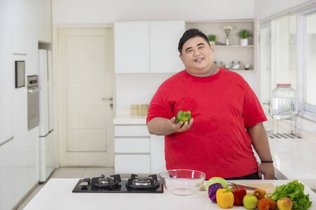 Picture of happy fat man holding a green paprika while preparing to make a healthy salad in the kitchen
