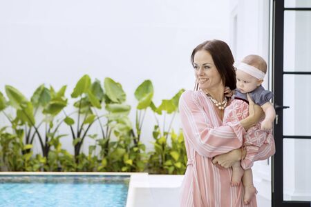 Picture of happy woman holding her baby while standing near the swimming pool 写真素材