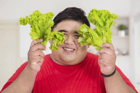 Close up of overweight man smiling at the camera while holding fresh lettuce in the kitchen