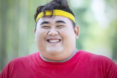 Close up of obese man smiling at the camera while wearing sportswear in the park