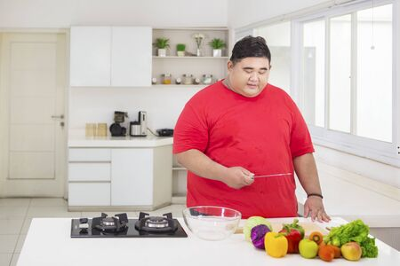 Overweight man holding a knife while preparing healthy salad in the kitchen