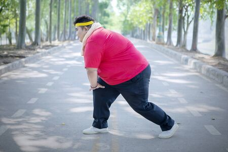Side view of a young fat man doing warm up before jogging in the park