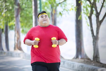 Picture of Asian fat man holding two dumbbells while running in the park Reklamní fotografie
