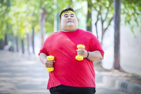 Overweight man carrying two dumbbells while running in the park
