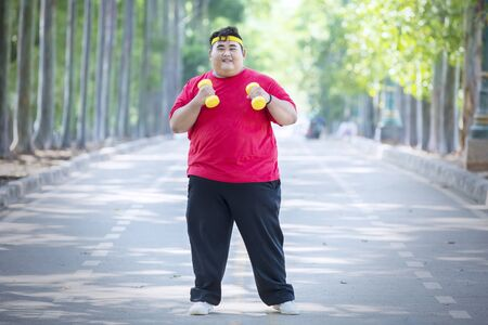 Picture of young fat man exercising with dumbbells while standing on the road