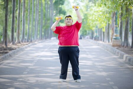 Picture of young fat man lifting two dumbbells while standing on the road Reklamní fotografie
