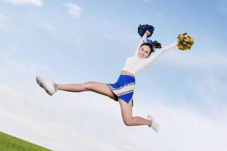 Low angle view of happy cheerleader girl lifting pom poms while jumping under blue sky in the meadow