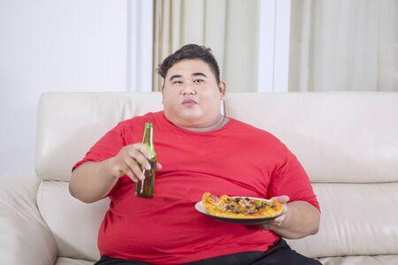 Hombre gordo joven que ve la televisión mientras come pizza y bebe cerveza en el sofá. Disparo en casa