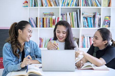 Group of female teenagers looks happy while studying together in the library with bookcase background Stok Fotoğraf