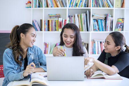 Gruppe weiblicher Teenager sieht glücklich aus, während sie zusammen in der Bibliothek mit Bücherregal-Hintergrund lernen Standard-Bild