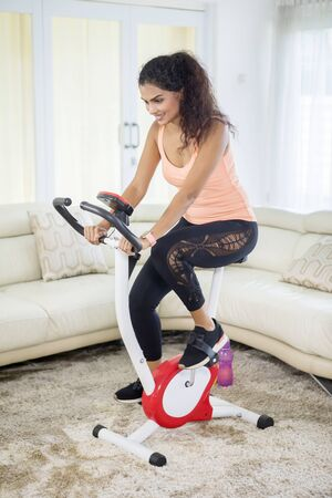 Portrait of young Indian woman doing a workout with an exercise bike in the living room. Shot at home