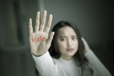 Image of sad teenage girl showing help word on her palm while sitting in the dark room