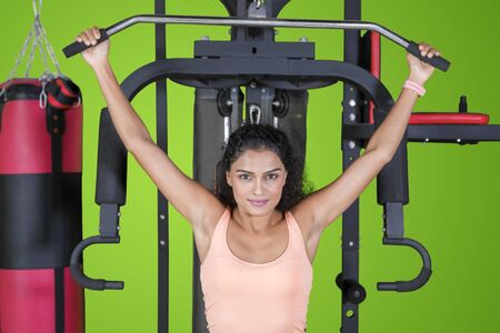 Picture of wavy hair woman exercising with fitness machine in the studio with green screen background