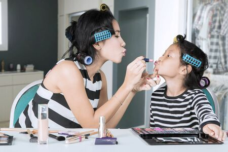Picture of young mother applying a lipstick to her daughters lips while doing makeup at home Reklamní fotografie