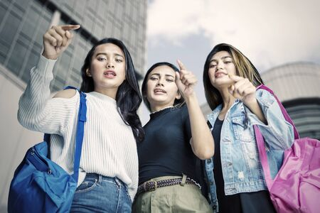 Vista de ángulo bajo de mujeres adolescentes intimidando a alguien mientras apunta a la cámara. Disparo al aire libre
