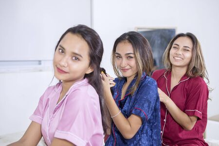 Group of happy teenage girls tying hair to each other in the bedroom while smiling at the camera. Shot at home Stock Photo