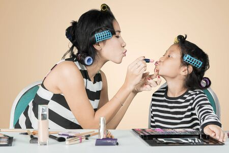 Portrait of a young woman applying a lipstick to her daughters lips while doing makeup in the studio