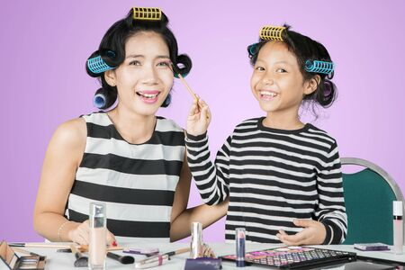 Picture of cheerful little girl applying a mascara to her mother while doing makeup in the studio