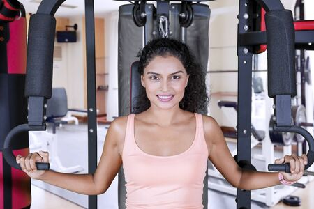 Picture of curly hair woman smiling at the camera while exercising with a fitness machine in the gym center Imagens