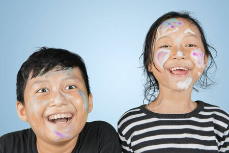 Picture of two little children smiling at the camera with face painting in the studio