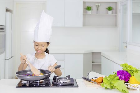 Picture of a little girl doing stir fry vegetables while standing in the kitchen. Shot at home