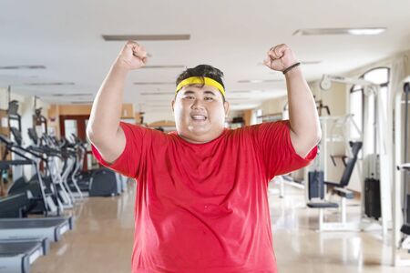 Overweight man lifting hands to expressing his success to lose weight while standing in the gym center Фото со стока