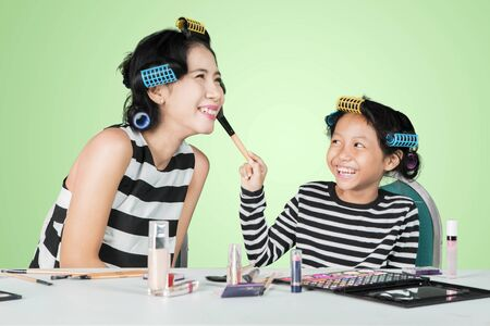 Little girl looks happy while applying powder on her moms face in the studio with green screen