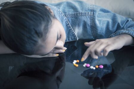 Addicted teenage girl looks depressed while counting drugs on the table at home Zdjęcie Seryjne