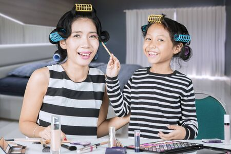 Picture of happy little girl applying a mascara to her mother while doing makeup in the Reklamní fotografie