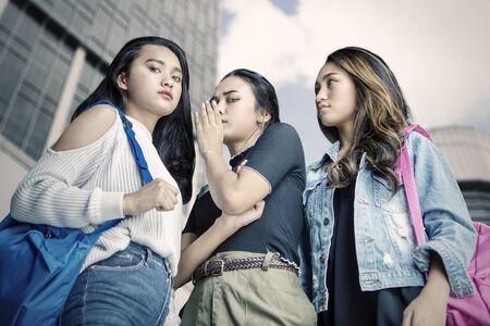 Grupo de mujeres adolescentes chismeando a alguien mientras mira a la cámara Foto de archivo