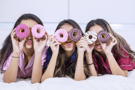 Group of teenage girls covering their eyes with donuts while lying on the bed. Shot at home