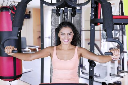 Picture of sporty woman smiling at the camera while exercising with a fitness machine in the gym cente