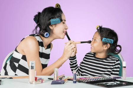 Picture of young woman and her daughter looks happy while doing makeup for each other in the studio