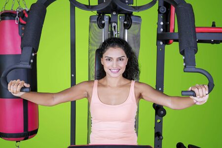 Picture of sporty woman exercising with a fitness machine in the studio with green screen studio