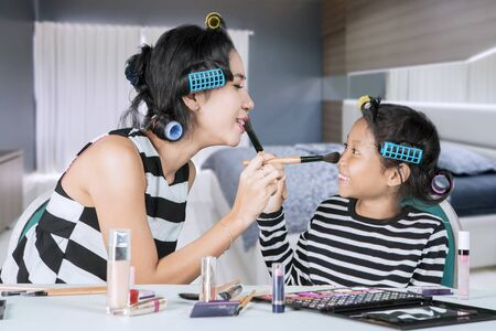 Picture of little child and her mother looks happy while doing makeup for each other in the bedroom