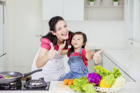 Young mother and her daughter smiling at the camera while showing thumbs up after cooking in the kitchen