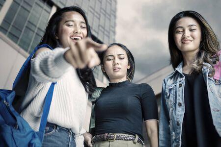 Vista de ángulo bajo de tres adolescentes burlándose de alguien mientras apunta a la cámara. Disparo al aire libre