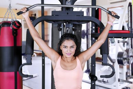 Picture of wavy hair woman exercising with fitness machine at the gym center