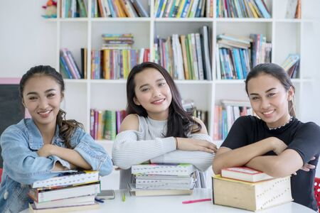 Group of happy teenager girls looking at the camera while studying in the library with bookcase background