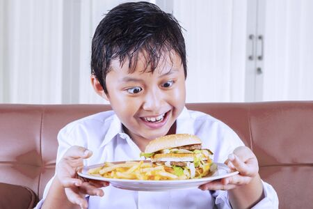 Close up of a little boy have a great desire to eat while holding a plate of burger and french fries while sitting on the couch