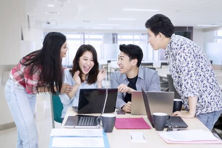 Group of young business people looks happy while working with laptops in the office
