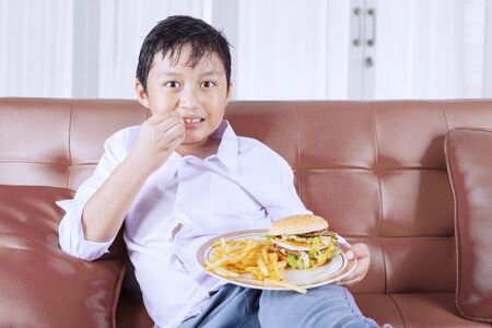 Portrait of fat little boy eating burger and french fries while sitting on the couch and watching TV. Shot at home