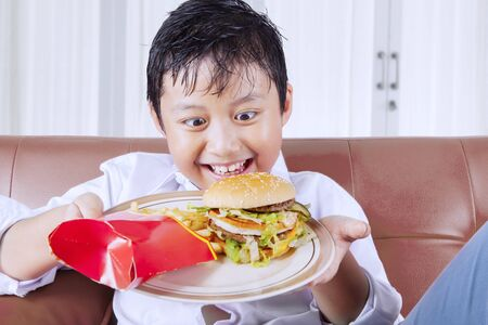 Greedy little boy looking at a plate of burger and french fries while sitting on the couch