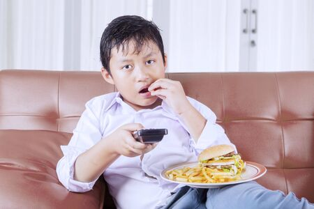 Portrait of a fat little boy eating junk foods while sitting on the couch and watching TV. Shot at home