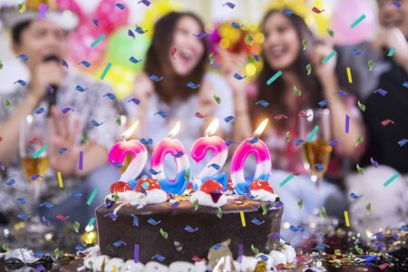 Close up of candles shaped number 2020 on birthday cake with blurred birthday party background