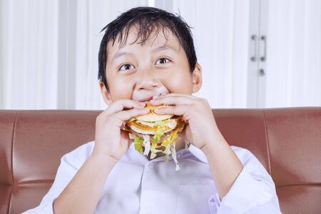 Close up of a voracious little boy eating a burger while sitting on the sofa. Shot at home
