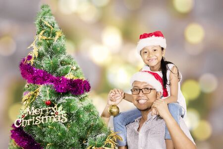 Young father and his daughter smiling at the camera while standing near a Christmas tree in the studio