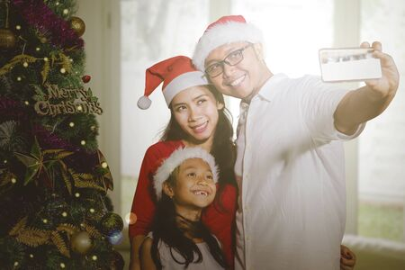 Young parents with their daughter taking a selfie photo together by using a smartphone near a Christmas tree